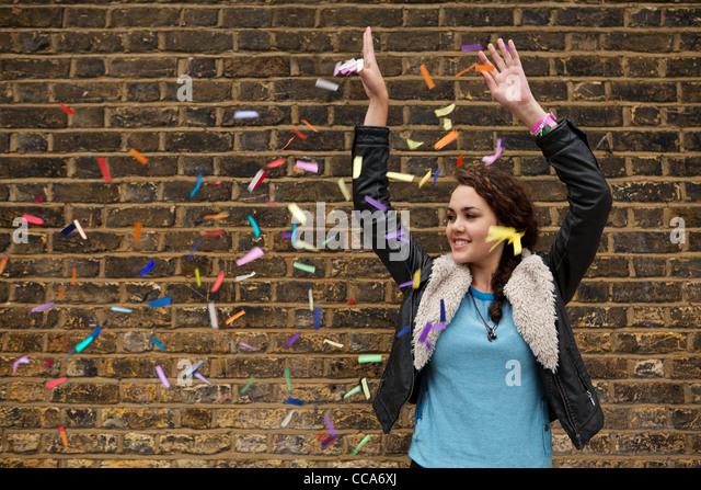 Junge Frau fallen bunte Konfetti gegen Mauer Stockbild