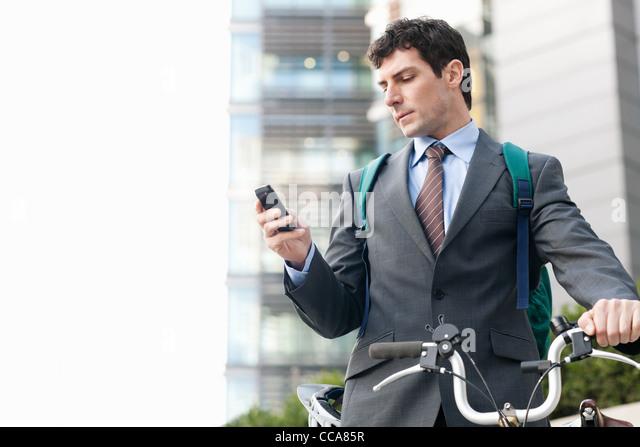 Mitte adult Geschäftsmann mit Fahrrad mit Handy Stockbild