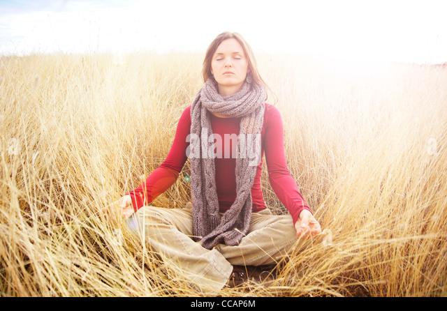 Schöne junge Frau, die in strahlendem Licht in eine lange Wiese Ruhe meditieren Stockbild