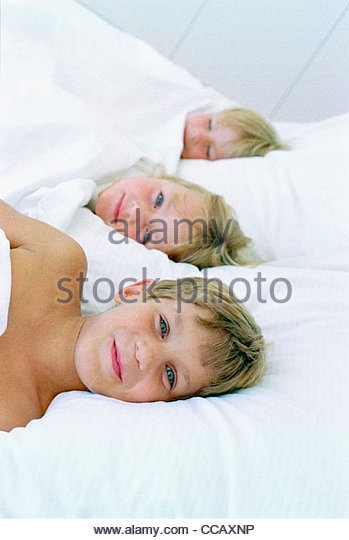 Kinder mit im Bett zusammen unter der Decke Stockbild