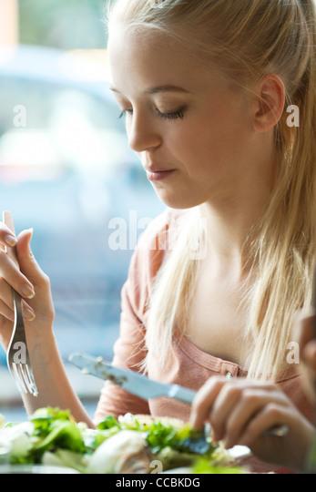 Junge, blonde Frau mit Messer und Gabel essen Stockbild
