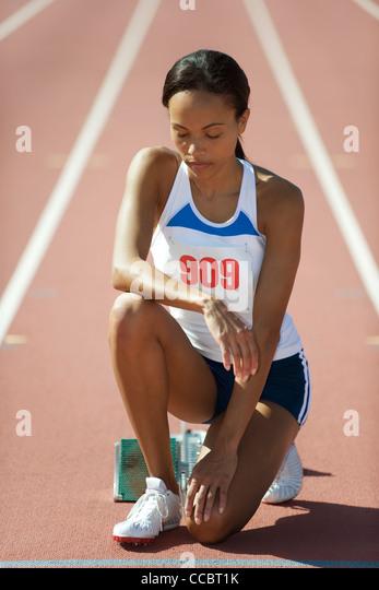 Weibliche Läufer an der Startlinie mit geschlossenen Augen hocken Stockbild