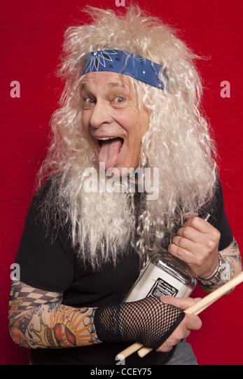 Porträt von senior Musiker halten Drum Stick und Alkohol Flasche während der Zunge Stockbild