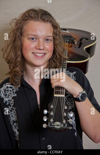 Porträt von lächelnden jungen Musiker mit Gitarre Stockbild