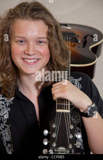 Porträt von lächelnden jungen Musiker mit Gitarre über Schulter Stockbild