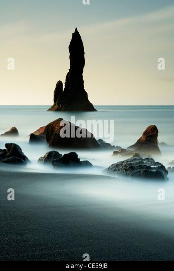 Wellen im ganzen schwarzen vulkanischen Felsnadeln entlang der Vik in Island Stockbild
