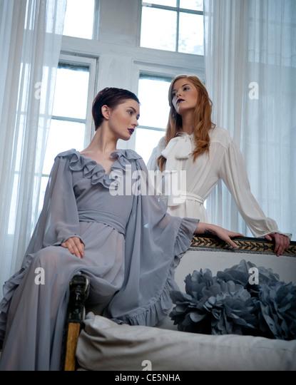 Zwei Frauen vor einem Fenster Stockbild