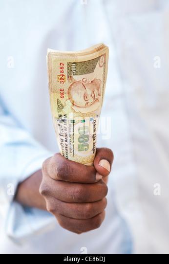 Indische mans Hand hält eine Reihe von 500 Rupien Noten Stockbild