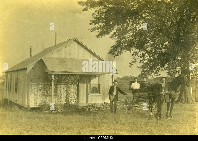 Siedler vor aus Holz nach Hause auf Gehöft während des späten 1800 s mit Pferd und Wagen buggy Stockbild