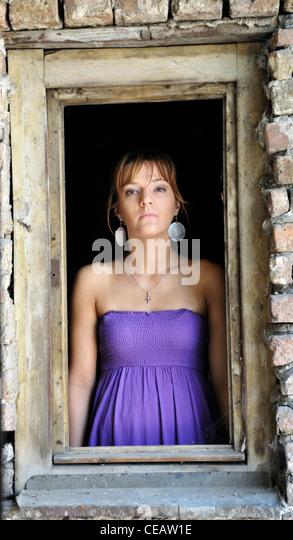Porträt einer jungen Frau steht im Fensterrahmen Stockbild
