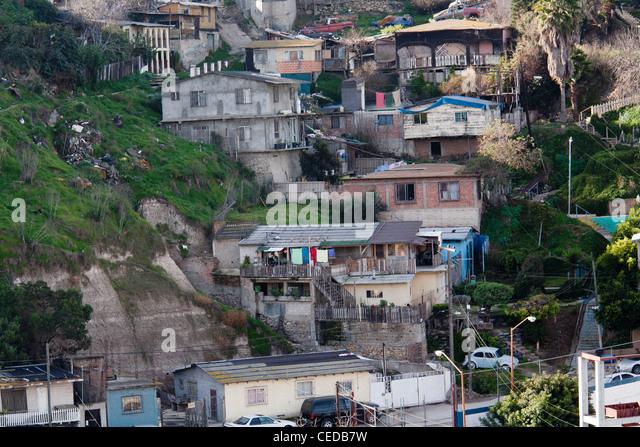 Tijuana, Baja California, Mexiko - eine Nachbarschaft direkt hinter dem Grenzzaun, der den Vereinigten Staaten und Stockbild