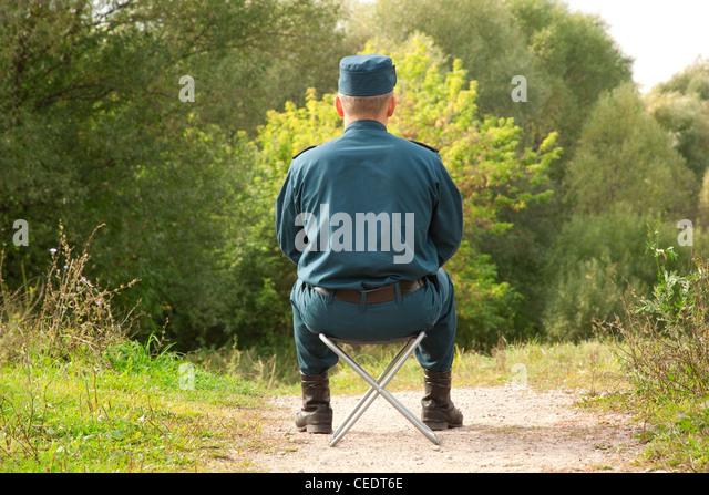 militärische Mann sitzt wieder auf dem Camp-Stuhl im freien Stockbild