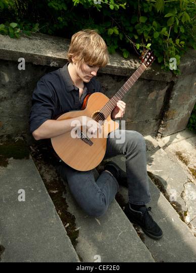 Junger Mann sitzt auf alte Zement-Treppe, eine klassische Gitarre zu spielen. Stockbild