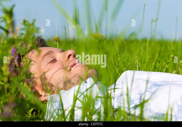 Junger Mann liegend auf einem Rasen oder Wiese im Sommer träumen und schlafen Stockbild