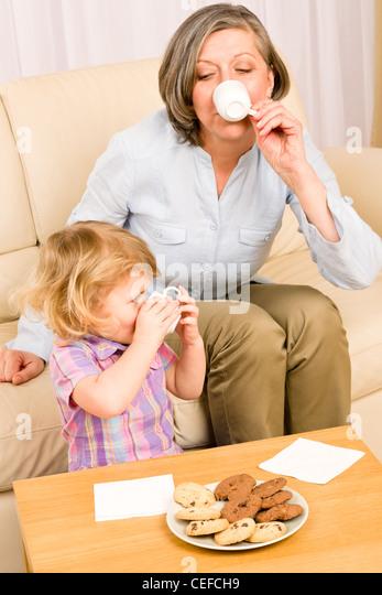 Kleine Enkelin mit Großmutter Essen Cookies Getränk Teetasse zusammen Stockbild