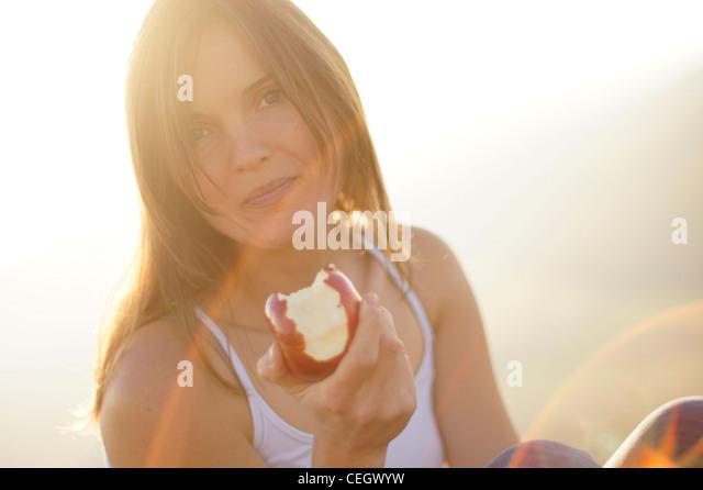 Schöne junge Frau, die einen saftigen roten Apfel zu essen, im schönen goldenen Licht der untergehenden Stockbild
