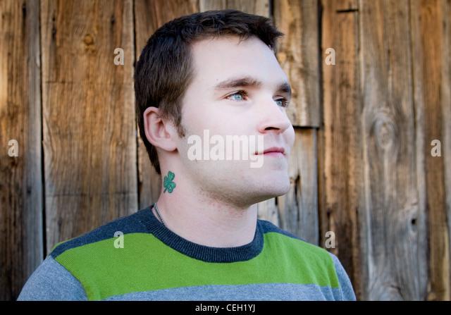 Porträt eines Mannes mit einem Kleeblatt Tattoo aus Blick in die Ferne Stockbild
