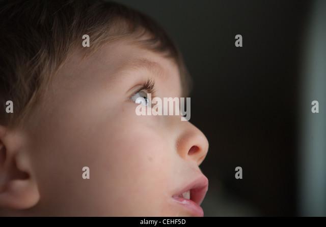 Nahaufnahme eines zwei Jahre alten Jungen nachschlagen durch Fenster, Profil des Gesichts. Stockbild