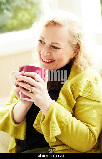 Frau mit Getränk entspannen Stockbild