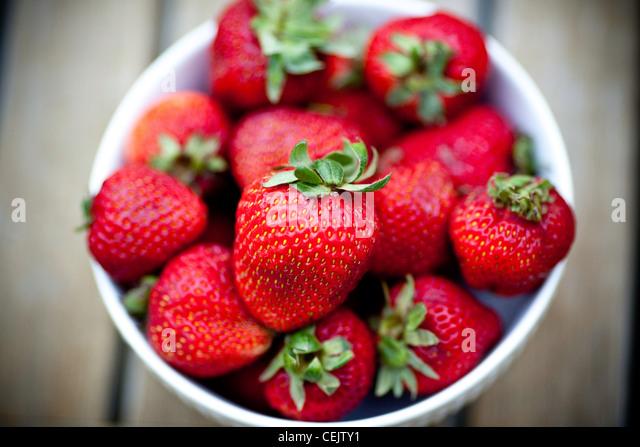 Erdbeeren in eine Schüssel geben Stockbild