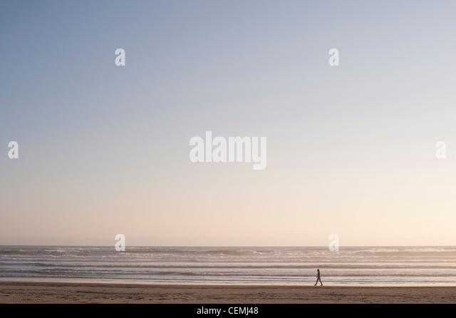 Frau allein in ruhige Szene Ozeanstrand entlang spazieren Stockbild