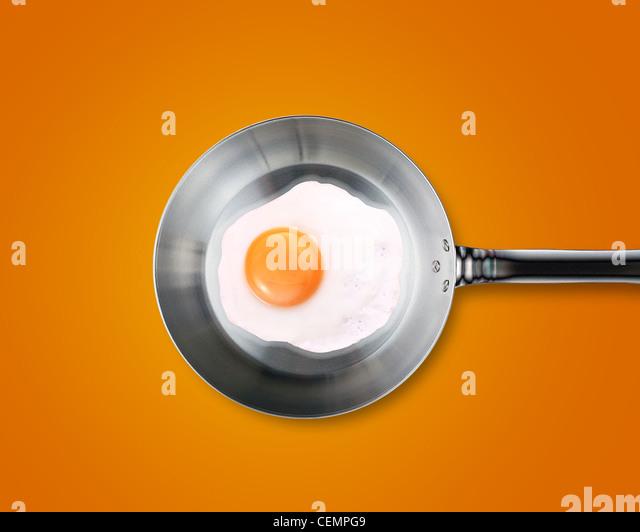 Spiegeleier in einer Pfanne auf orangem Hintergrund Stockbild