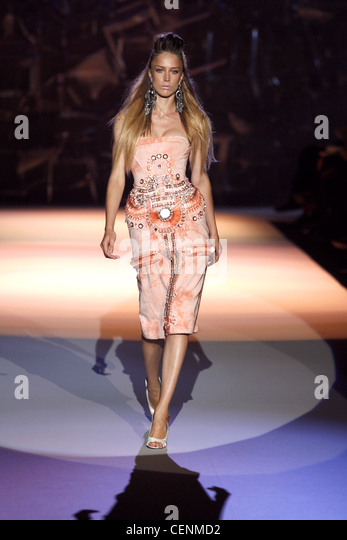 Quiffed Haar, ethnische Ohrringe, Pfirsich verziertes Kleid mit print Kleid Stockbild