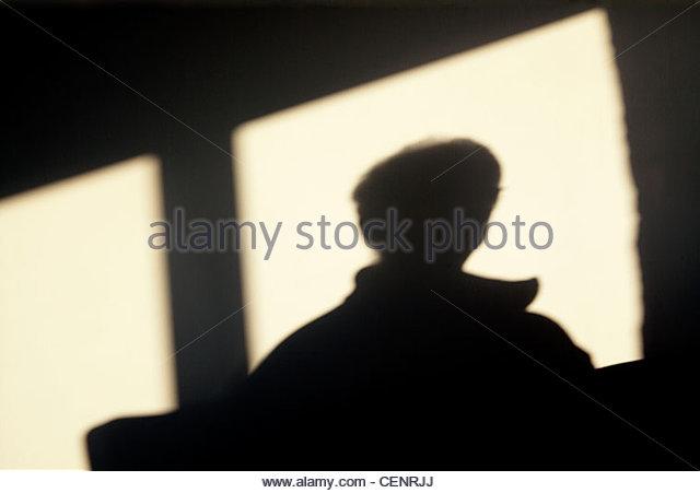 Silhouette einer Person aus einem Fenster schauen Stockbild