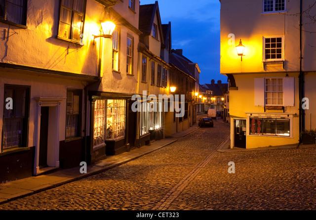 Elm Hill, gepflasterten eine historische Gasse mit vielen Bauten aus der Tudor-Zeit, in der Dämmerung beleuchtet. Stockbild