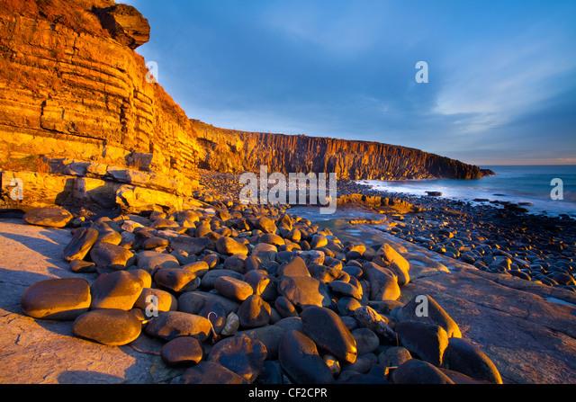 Dawn Licht erhellt die felsige Küste der Cullernose Punkt, in der Nähe von Dorf Craster an der Northumberland Stockbild