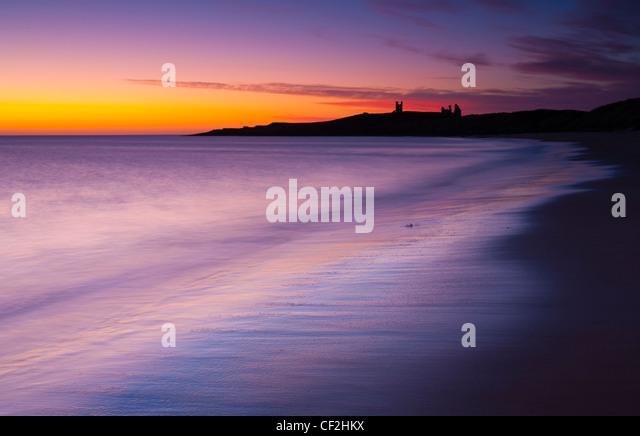 Eine bunte Anzeige von vor Sonnenaufgang Farben Popularitätswert auf dem nassen Sand Embleton Bay, überragt Stockbild