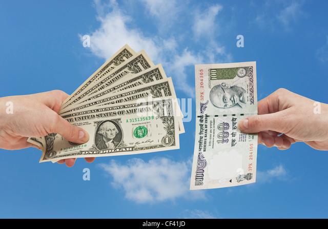 Fünf 1 US-Dollar-Scheine in der Hand gehalten werden. Auf der anderen Seite ist eine indische 100 Rupien Rechnung - Stock-Bilder