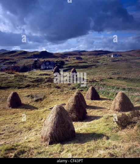 Blick über traditionelle, hand gesammelten Heuballen gegenüber der verstreuten Gemeinschaft von Lacasaidh Stockbild