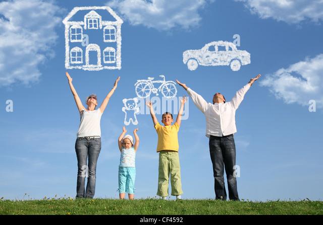 vierköpfige Familie auf Rasen mit Hände hoch und Traum Stockbild
