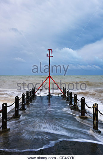 Wellen brechen, um ein roter Leuchtturm am Ende ein Wellenbrecher. Stockbild