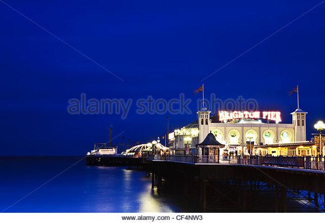 Vergnügungen und Sehenswürdigkeiten am Pier von Brighton nachts beleuchtet. Stockbild