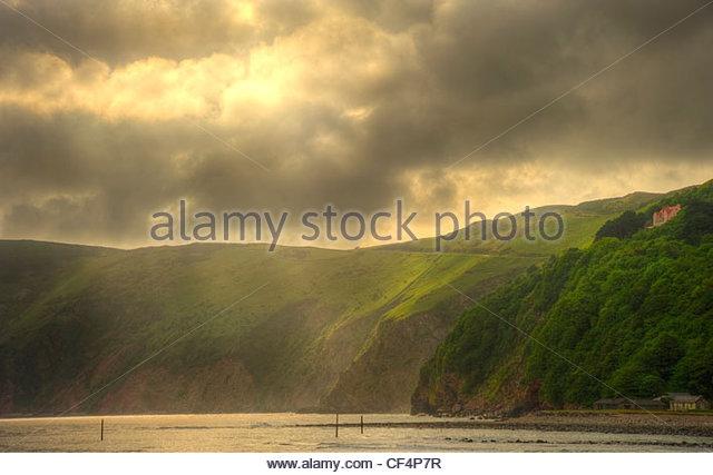 Lichtstrahlen durchbrechen Gewitterwolken über Lynmouth auf der Nord-Devon Küste bei Sonnenaufgang. Stockbild