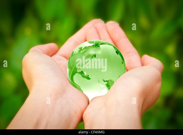 menschliche Hände sorgfältig mit Erde. Glas-Welt Stockbild