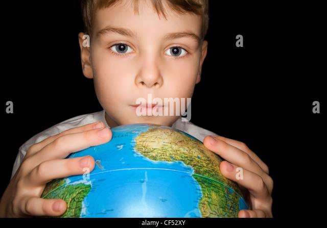 Junge hält in Händen über Globus der Welt auf schwarzem Hintergrund isoliert Stockbild