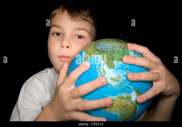 junge umarmen Globus der Welt auf schwarzem Hintergrund isoliert Stockbild