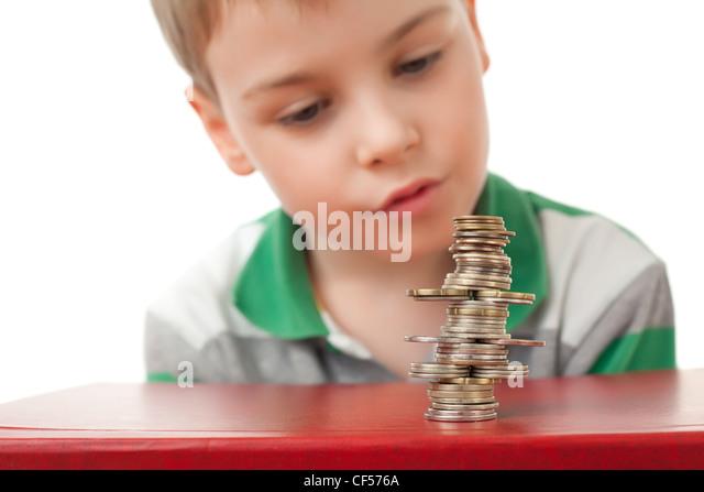 Junge im gestreiften T-shirt Blick auf Kurve Haufen von Münzen Münzen isoliert auf weißem Hintergrund Stockbild