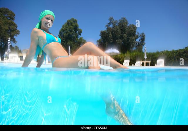 Frau im Badeanzug sitzt tagsüber im Pool und Bein ins Wasser setzen Stockbild