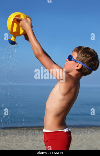 Junge steht am Strand tagsüber und schüttet Sand Gießkanne anhebende hand Stockbild