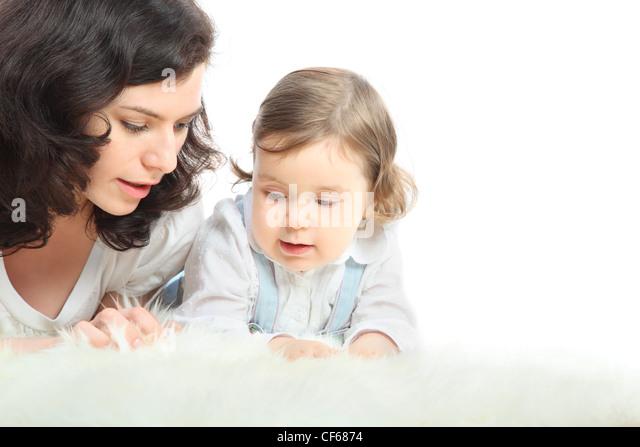 Nachdenklich Mutter und ihrer kleinen Tochter liegen auf weißen flauschigen Teppich Stockbild
