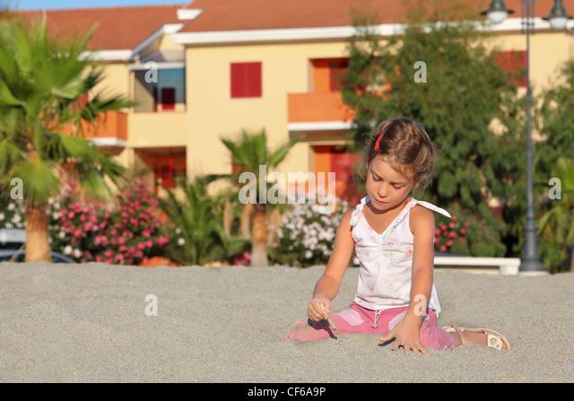 Mädchen sitzt tagsüber am Strand und dazulernen führt Stöckchen auf sand Stockbild