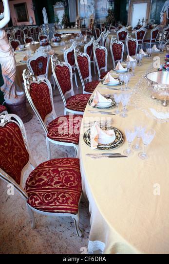 Großer Esstisch mit leeren Geschirr: Teller mit Platzdeckchen, Gabeln, Messer und Becher Stockbild