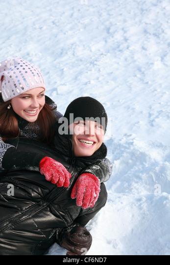 Junge Menschen liegen seitlich auf Schnee, lachen und zur Seite schauen Stockbild