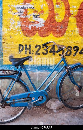 Traditionelle indische Womans Fahrrad gegen einen gelb gestrichenen Wand. Andhra Pradesh, Indien Stockbild