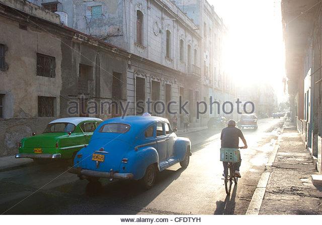 Straßenszene gebadet im morgendlichen Sonnenlicht zeigt alte amerikanische Autos und Radfahrer, Havanna, Kuba, Stockbild