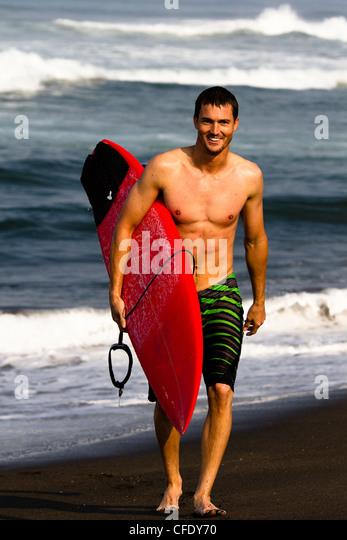 Eine männliche Surfer Boardshorts tragen nähert sich der Strand von Pasquales, Mexiko eine rote Surfbrett Stockbild
